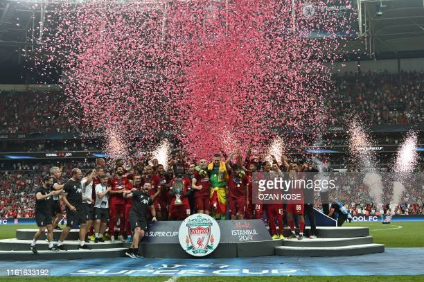 Liverpool's team poses with the trophy after winning the UEFA Super Cup 2019 football match between FC Liverpool and FC Chelsea at Besiktas Park...
