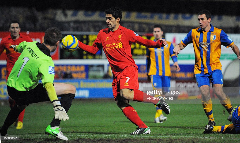 """Liverpool's Uruguayan forward Luis Suarez (C) appears to handle the ball in the lead up to his goal during the FA Cup third round football match between Mansfield Town and Liverpool at Field Mill in Mansfield, central England, on January 6, 2013. Liverpool won the match 2-1. USE. No use with unauthorized audio, video, data, fixture lists, club/league logos or """"live"""" services. Online in-match use limited to 45 images, no video emulation. No use in betting, games or single club/league/player publications."""