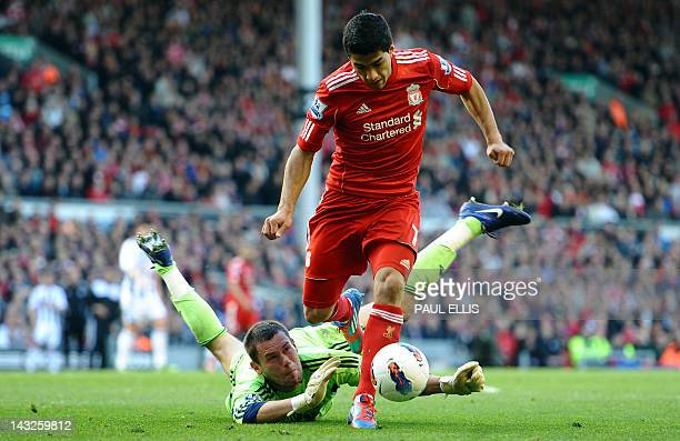 Liverpool's Uruguayan forward Luis Suarez takes the ball past West Bromwich Albion's English goalkeeper Ben Foster during the English Premier League...
