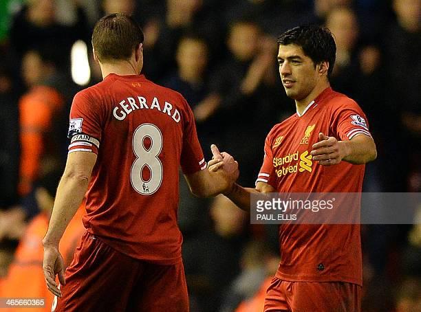 Liverpool's Uruguayan striker Luis Suarez celebrates with Liverpool's English midfielder Steven Gerrard after the English Premier League football...