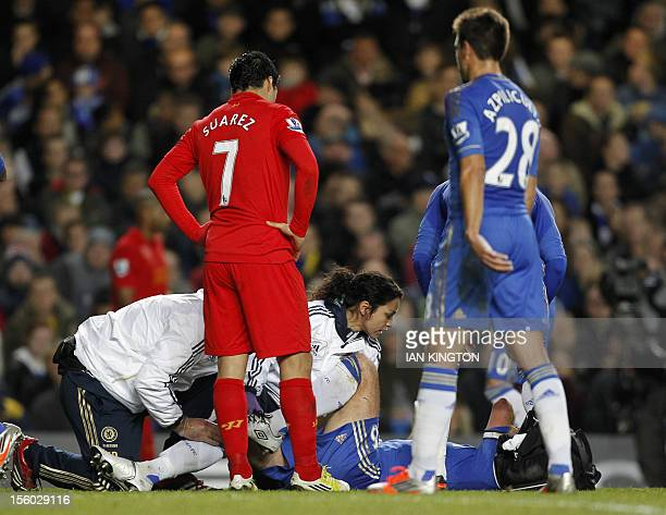 Liverpool's Uruguayan striker Luis Suarez checks on Chelsea's English defender John Terry as he is attended to by club physio Eva Carneiro after...