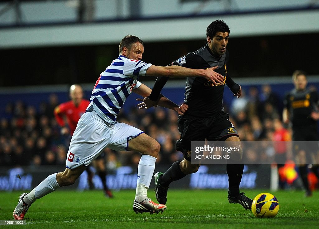 """Liverpool's Uruguayan striker Luis Suarez (R) runs past Queens Park Rangers' English defender Clint Hill (L) on his way to scoring the opening goal against Queens Park Rangers during the Premiership match at Loftus Road in London on December 30, 2012. USE. No use with unauthorized audio, video, data, fixture lists, club/league logos or """"live"""" services. Online in-match use limited to 45 images, no video emulation. No use in betting, games or single club/league/player publications."""