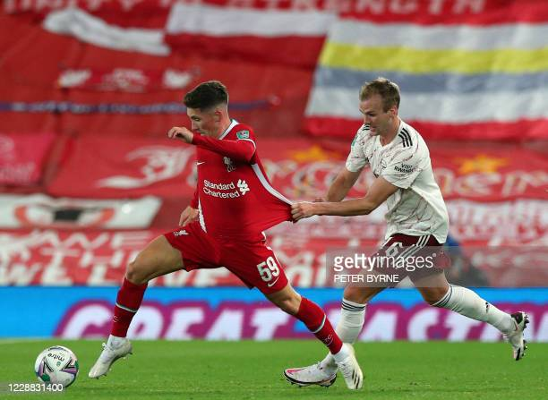 Liverpool's Welsh midfielder Harry Wilson is pulled back by Arsenal's English defender Rob Holding during the English League Cup fourth round...
