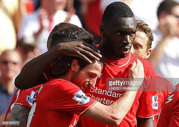 Liverpool's Welsh midfielder Joe Allen celebrates scoring his team's first goal with Liverpool's Zaireborn Belgian striker Christian Benteke during...