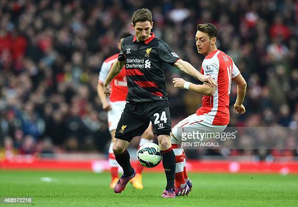 Liverpool's Welsh midfielder Joe Allen vies with Arsenal's German midfielder Mesut Ozil during the English Premier League football match between...
