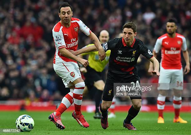 Liverpool's Welsh midfielder Joe Allen vies with Arsenal's Spanish midfielder Santi Cazorla during the English Premier League football match between...
