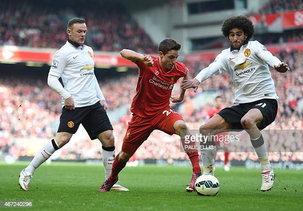 Liverpool's Welsh midfielder Joe Allen vies with Manchester United's English striker Wayne Rooney and Manchester United's Belgian midfielder Marouane...