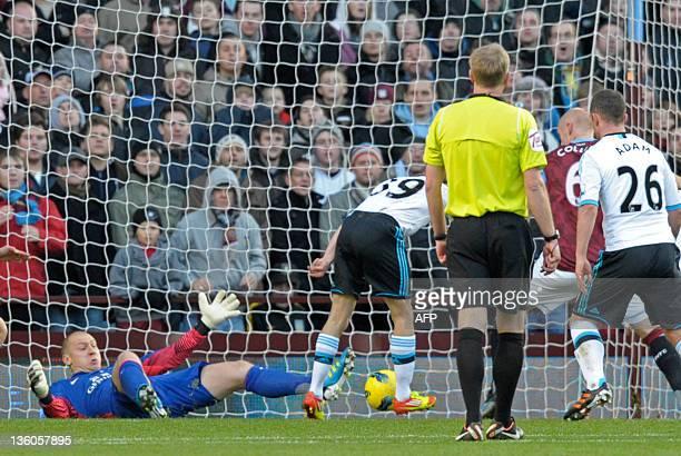 Liverpool's Welsh striker Craig Bellamy scores the opening goal past Aston Villa's US goalkeeper Bradley Guzan during the English Premier League...