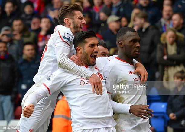 Liverpool's Zaireborn Belgian striker Christian Benteke celebrates with Liverpool's English midfielder Adam Lallana and Liverpool's German midfielder...