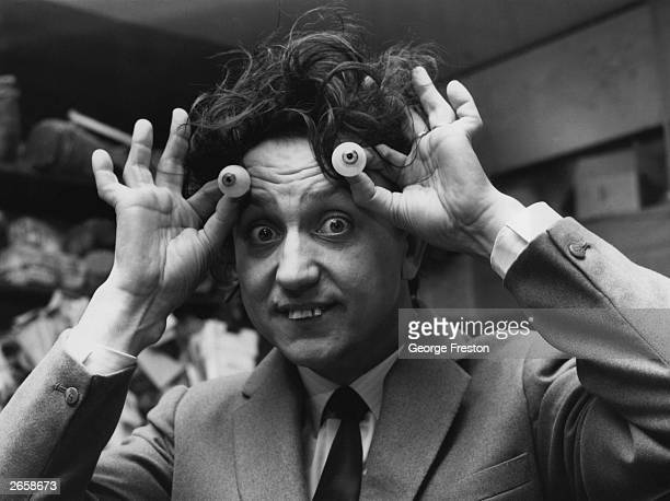 Liverpudlian comedian Ken Dodd checking a pair of eyes for correct colouring at Madame Tussaud's Waxworks Museum London