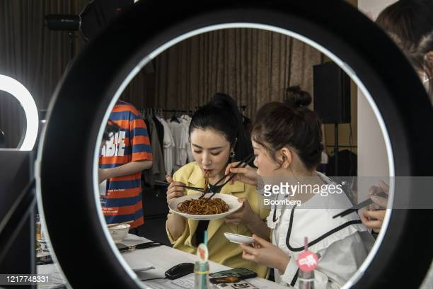 Livestreamer Huang Wei, known professionally as Viya, center, samples a plate of noodles during a special livestreaming event arranged by Qianxun...