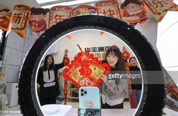 Livestreamer sells Chinese New Year decorations as she live streams video on a smartphone before the Chinese New Year, the Year of the Ox, on January...