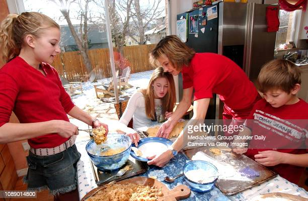 Livia Hooson left peels dough off a mixer as her mom Ann center sister Allie sitting and brother Jack prepare pierogi in their Boulder home on a...