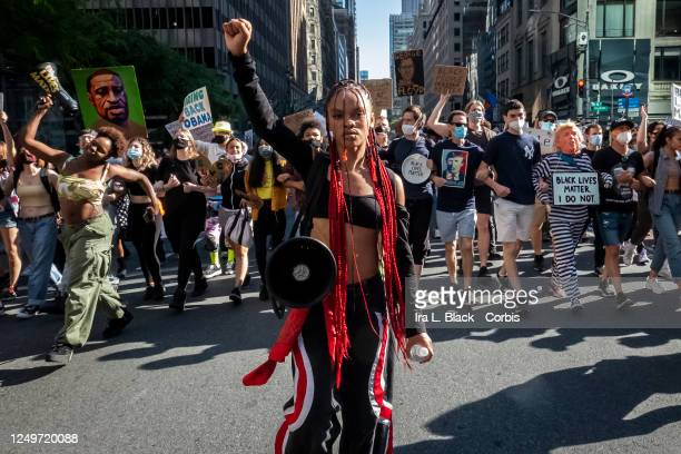 Livia Johnson, an organization leader for Warriors in the Garden holds a up her hand in a raised fist as she stands in front of hundreds of...