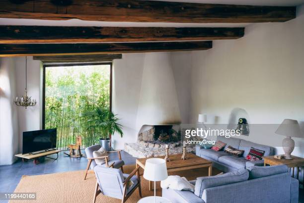 living area in traditional spanish farmhouse - two seater sofa stock pictures, royalty-free photos & images
