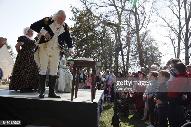 Living history interpreterÊDean Malissa who portrays George Washington cut a cake with his sword during a ÒBirthday Cake with Gen WashingtonÓ event...