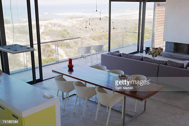living room and dining room with large windows and view of sand and water - big tom stock pictures, royalty-free photos & images