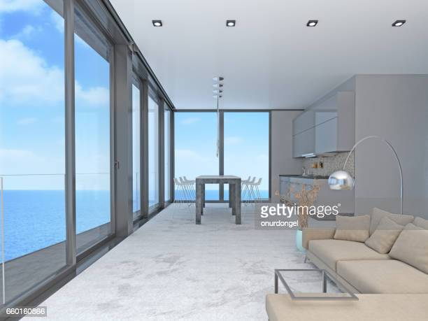 Living room and kitchen with windows and view of sea