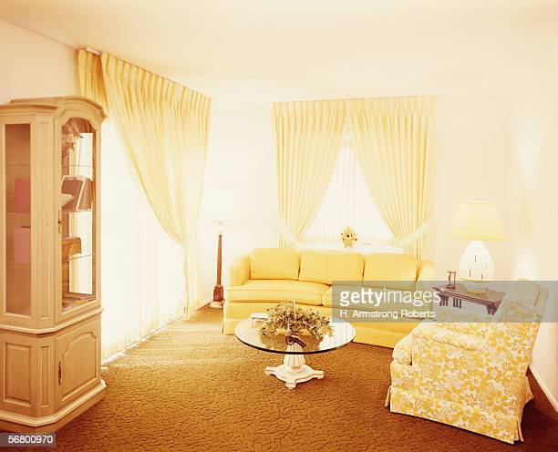 Living room interior with gold carpet and yellow couch