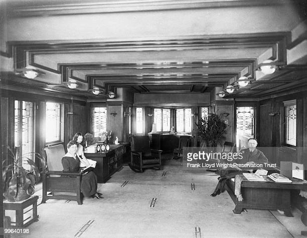 Living room looking west with Wilber family seated in original furnishings Rockers original to House in prow Chicago Illinois 1916
