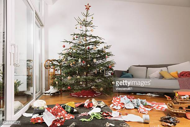 Living room on Christmas morning with torn up wrapping paper in front of the tree