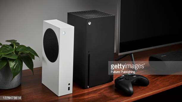 Living room with a pair of Microsoft home video game consoles, including an Xbox Series S and Xbox Series X, alongside a television and soundbar,...