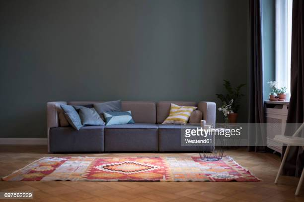 living room with couch and carpet - sofa stock-fotos und bilder