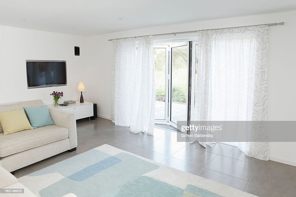 Living room with glass door to garden ajar : Stock Photo
