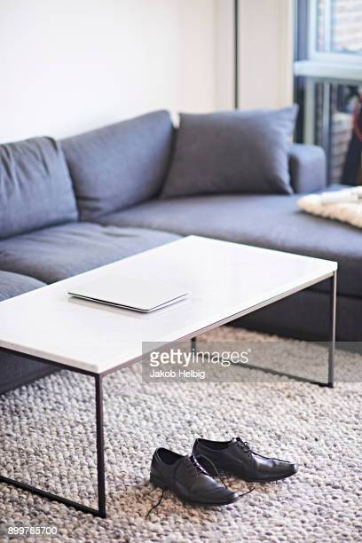 Living room with laptop on coffee table and mens shoes on rug