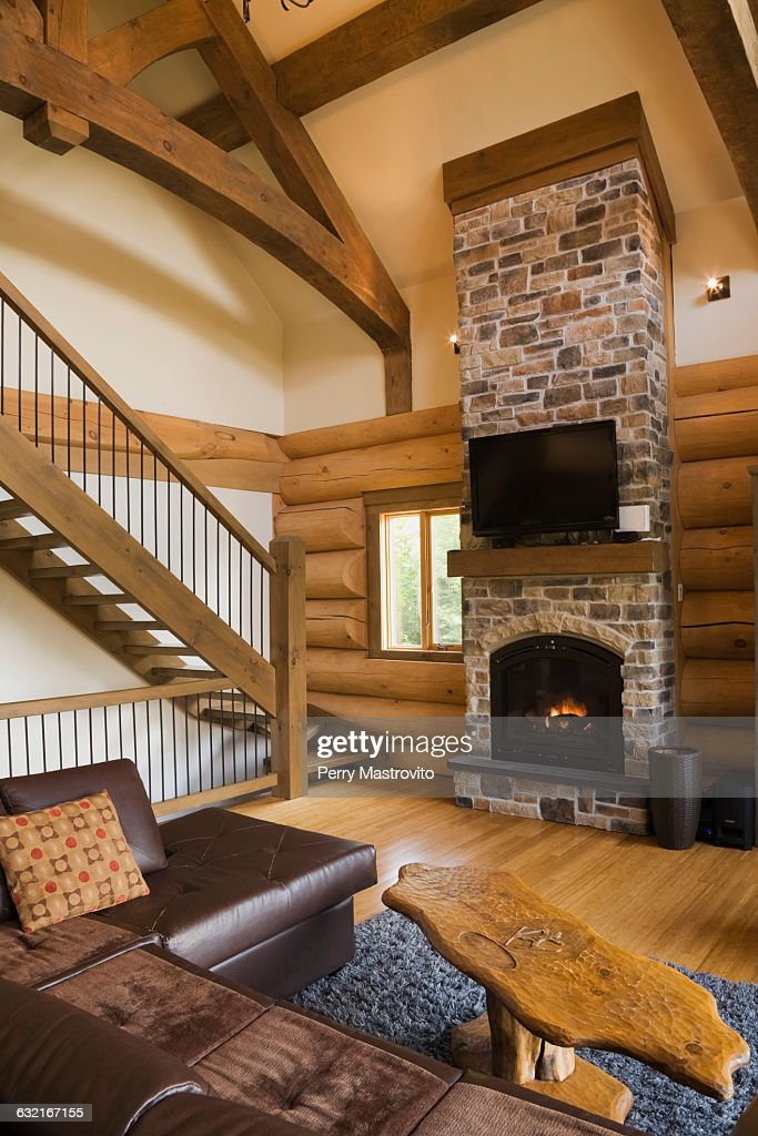 Living Room With Leather Sofa And Coffee Table In Front Of Stone Fireplace Stairs Iron Railings Scandinavian Cottage Style Log Home