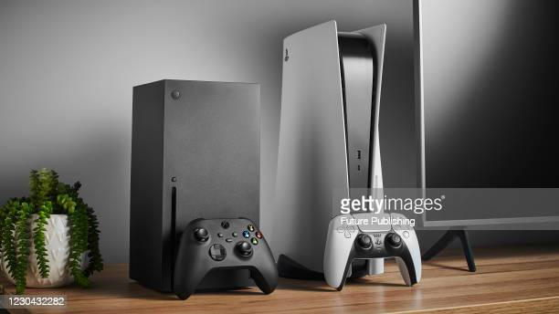 Living room with Microsoft Xbox Series X and Sony PlayStation 5 home video game consoles alongside a television and soundbar, taken on November 3,...