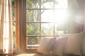 Living room with part of sofa in sunny day and white curtain.