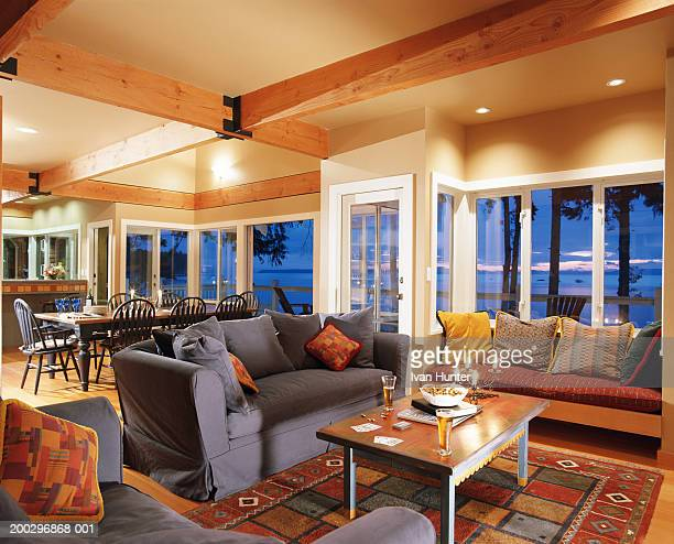 living room with view to ocean, beer on table, twilight - man cave stock pictures, royalty-free photos & images