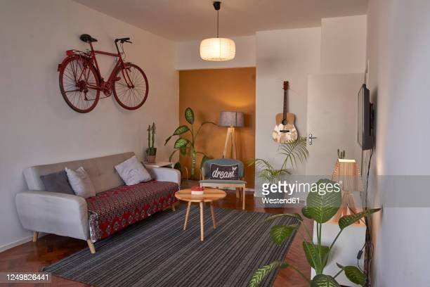 living room with vintage bicycle hanging on the wall - hanging stock pictures, royalty-free photos & images