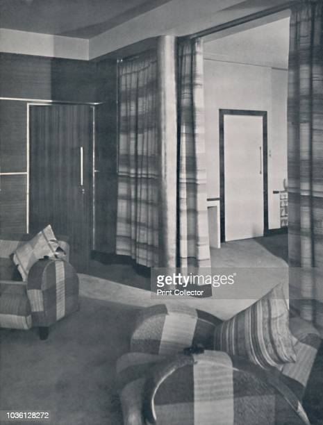 Livingroom in a London house designed by Raymond McGrath ARIBA' 1936 Entrance door on left is faced with Venesta Australian walnut ply walls in same...