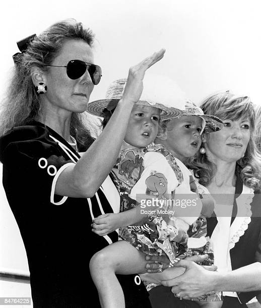 Liz Allison wife of Davey Allison waves a salute to her departed husband at the Memorial Service on July 26 1993 in Talladega Alabama Liz is holding...
