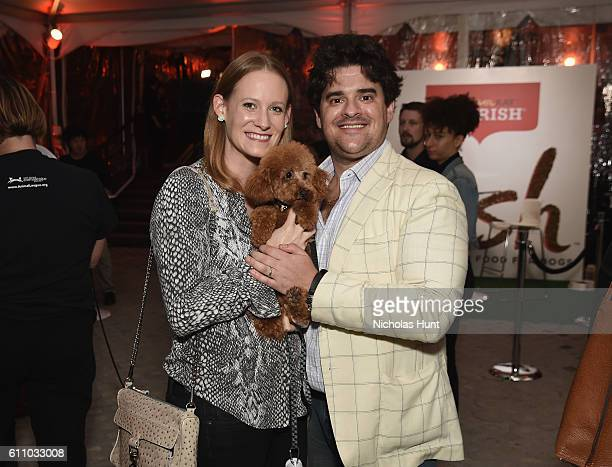 Liz Bresler and Alex Bresler pose with Chase the dog during the celebration of the launch of Rachael Ray's Nutrish DISH with a Puppy Party on...