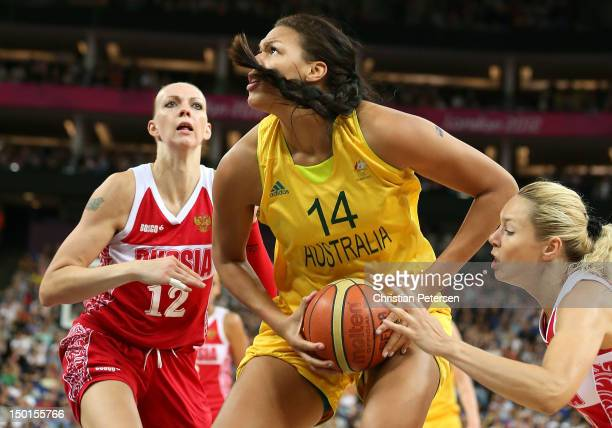 Liz Cambage of Australia attempts a shot in the first half against Irina Osipova and Nadezhda Grishaeva of Russia during the Women's Basketball...