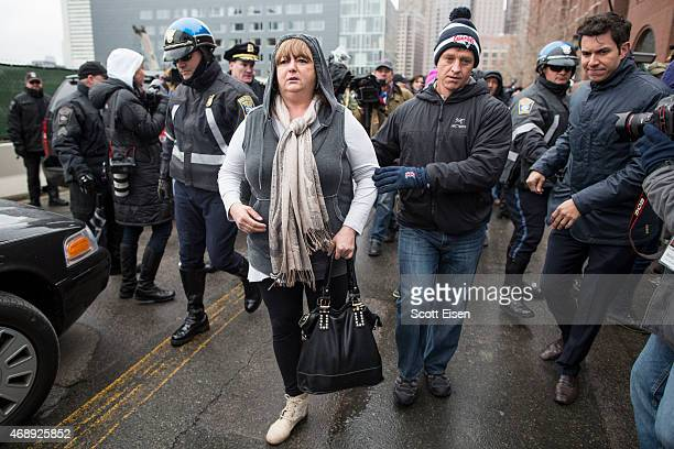 Liz Norden walks with Massport Fire Lt Michael Ward after a press conference outside of John Joseph Moakley United States Courthouse following a...