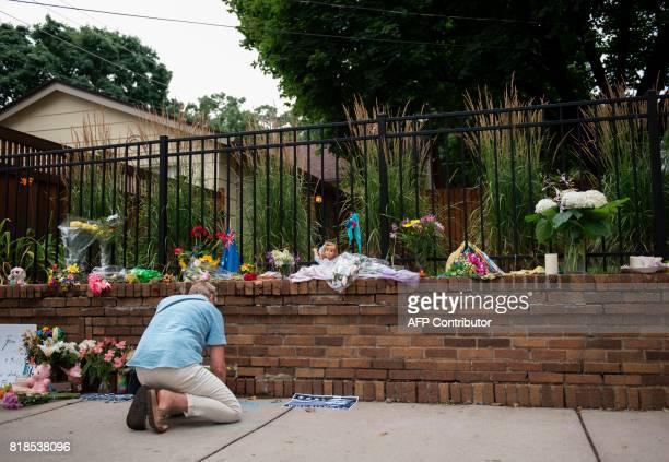 Liz Reyer who attended yoga with Justine Damond writes 'Justine is Love' in chal near a memorial for Justine Damond on July 18 2017 in Minneapolis...