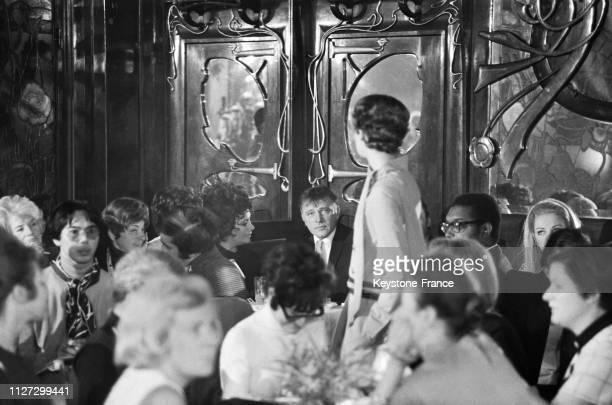 Liz Taylor et Richard Burton assis parmi les spectateurs regardent défiler une mannequin chez 'Maxim's' à Paris France le 22 janvier 1968