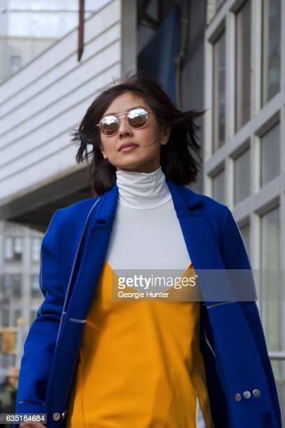 Liz Uy is seen at Spring Studios outside the Phillip Lim show wearing full length bright blue coat with white lines white and orange dress with...