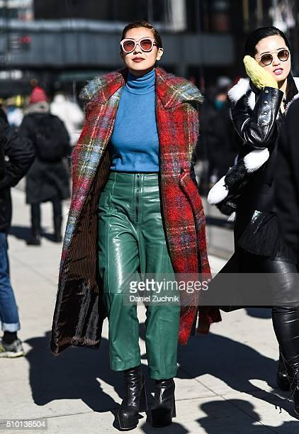 Liz Uy is seen outside the Tibi show wearing a plaid coat blue turtleneck sweater and green leather pants during New York Fashion Week Women's...