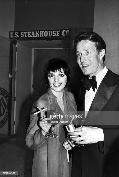 Liza Minnelli and designer Halston toasting their drinks while smoking cigarettes.