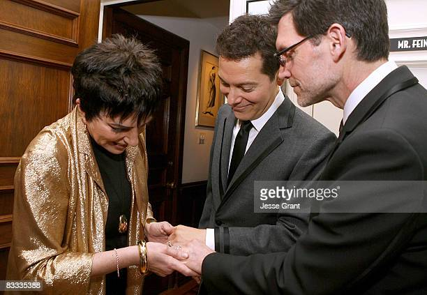 Liza Minnelli looks at Michael Feinstein and Terrence Flannery's wedding rings during their wedding ceremony held at a private residence on October...