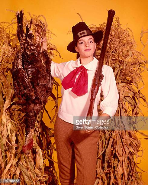 Liza Minnelli US actress and singer holding a rifle over her shoulder and wearing a black pilgrim's hat a white blouse with a red bow holding up a...