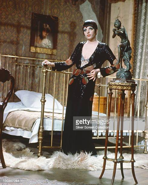 Liza Minnelli, US actress and singer, wearing a low-cut, long black dress, posing beside a bed in a publicity still issued for the film, 'Cabaret',...