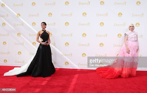 Lizzy Caplan and Lena Dunham arrive at the 66th Annual Primetime Emmy Awards at Nokia Theatre LA Live on August 25 2014 in Los Angeles California