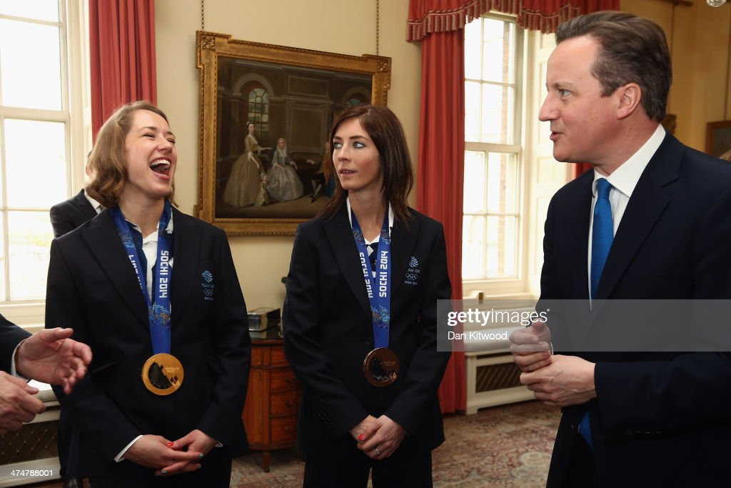 Lizzy Yarnold (L) and Eve Muirhead of Great Britain laugh with British Prime Minister David Cameron (R) at 10 Downing Street on February 25, 2014 in London, England. The Winter Olympic medal winners visited Downing Street today and met with the Prime Minister.