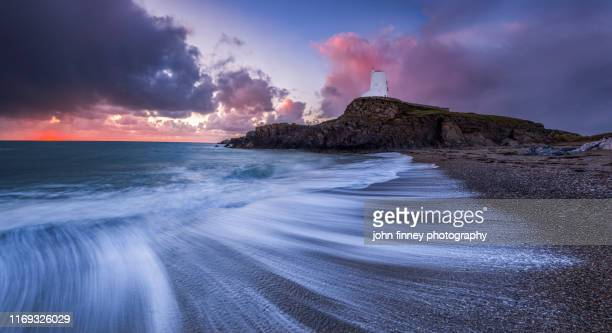 llanddwyn island lighthouse and beach with swishing water, bangor, caernarfon,, anglesey, united kingdom - coastline stock pictures, royalty-free photos & images